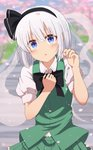 1girl absurdres arms_up bangs black_neckwear blue_eyes blurry blush bow bowtie cherry_blossoms day depth_of_field eyebrows_visible_through_hair green_skirt green_vest hair_between_eyes hair_ribbon hand_on_own_chest head_tilt highres holding_petal konpaku_youmu konpaku_youmu_(ghost) leaning_over looking_at_viewer outdoors parted_lips petals puffy_short_sleeves puffy_sleeves ribbon shirt short_hair short_sleeves silver_hair skirt sleeve_cuffs solo stairs standing taki_sandstone touhou upper_body vest white_shirt
