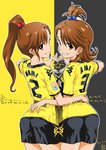 2girls ass borussia_dortmund brown_eyes commentary_request cowboy_shot from_behind futami_ami futami_mami grin hair_bobbles hair_ornament heart heart_hands heart_hands_duo idolmaster inoue_sora long_hair looking_at_viewer looking_back multiple_girls pantylines short_hair shorts siblings side_ponytail sisters smile soccer soccer_uniform sportswear star twins