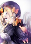 1girl abigail_williams_(fate/grand_order) black_dress black_hat blonde_hair blue_eyes blush bow commentary_request dress eyebrows_visible_through_hair eyes_visible_through_hair fate/grand_order fate_(series) frilled_sleeves frills hane_yuki hat highres keyhole long_hair looking_at_viewer object_hug orange_bow parted_lips polka_dot polka_dot_bow sleeves_past_fingers sleeves_past_wrists solo stuffed_animal stuffed_toy teddy_bear very_long_hair