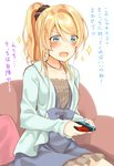 1girl ayase_eli blonde_hair blue_eyes blue_sweater blush cardigan commentary_request controller couch dress game_controller jewelry long_hair love_live! love_live!_school_idol_project mogu_(au1127) necklace nintendo_switch open_mouth playing_games ponytail scrunchie sitting solo sparkle sweater translation_request white