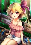 1girl ahoge bare_shoulders bench blonde_hair blurry blurry_background blush casual collarbone commentary contemporary crystal eyebrows_visible_through_hair flandre_scarlet hair_ribbon highres leaf looking_at_viewer no_hat no_headwear off-shoulder_shirt off_shoulder open_mouth pink_shirt red_eyes red_ribbon renka_(cloudsaikou) ribbon shirt short_hair short_shorts shorts side_ponytail sitting smile solo thighs touhou tree white_shorts wings