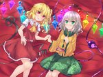 2girls ascot bangs bed_sheet blonde_hair blush bow commentary_request crystal eyebrows_visible_through_hair flandre_scarlet floral_print frilled_sleeves frills green_eyes green_skirt highres holding_hands interlocked_fingers komeiji_koishi laevatein long_hair looking_at_viewer lying miniskirt multiple_girls on_back one_side_up puffy_short_sleeves puffy_sleeves red_bow red_eyes red_skirt red_vest shirt short_sleeves silver_hair siohureiya skirt skirt_set smile third_eye touhou vest wavy_hair white_shirt wide_sleeves wings yellow_neckwear yellow_shirt